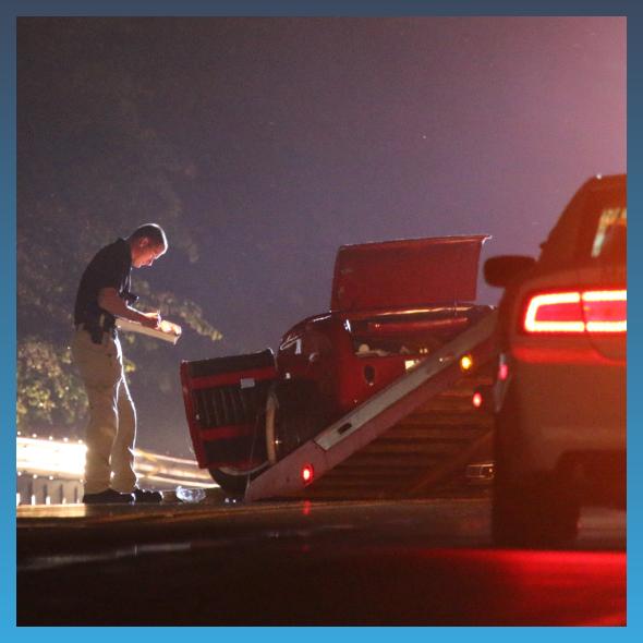 man inspecting car crash